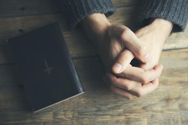 Homem orando perto do livro da bíblia
