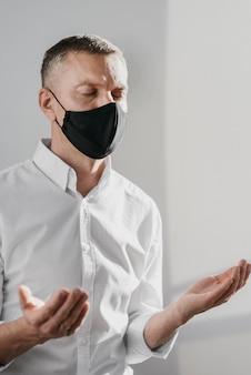 Homem orando sozinho em casa, usando uma máscara médica