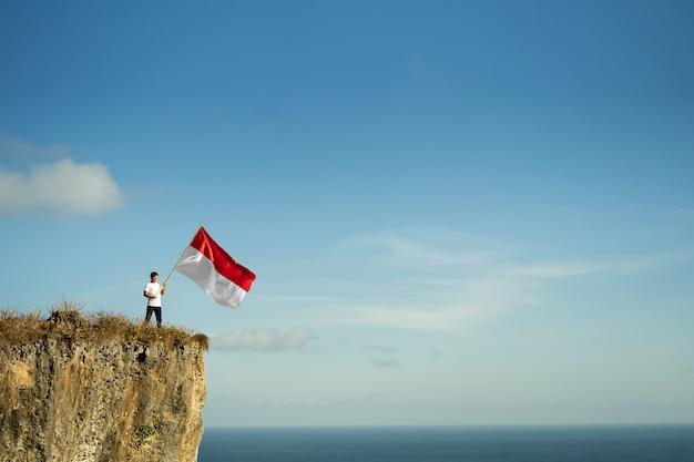 Homem orgulhoso da indonésia em um penhasco de praia erguendo bandeira vermelha e branca da indonésia
