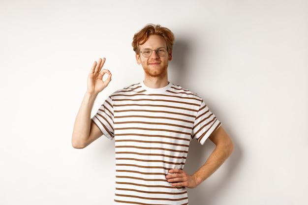 Homem orgulhoso e feliz com cabelo ruivo e óculos sorrindo, dando sinal de ok, elogiando algo excelente, dizendo sim ou bom, em pé sobre um fundo branco.