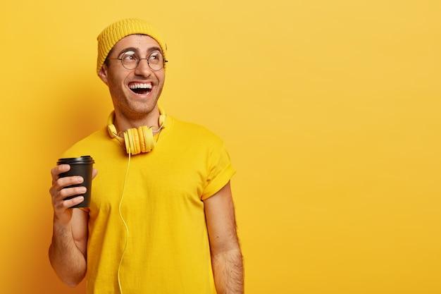 Homem otimista de óculos ri enquanto passa o tempo com os amigos durante a pausa para o café, segura um copo descartável, desvia o olhar