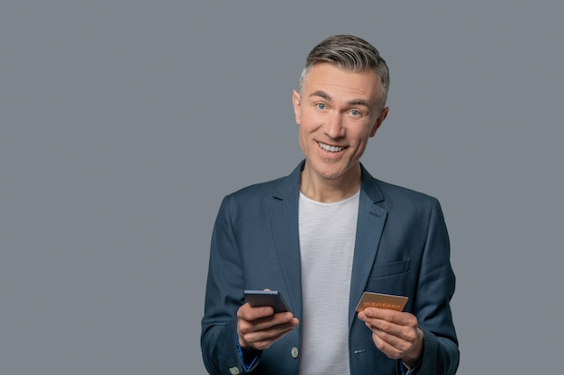 Homem otimista de sucesso com smartphone e cartão de crédito