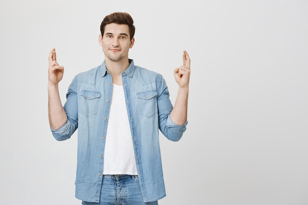 Homem otimista e esperançoso cruzando os dedos boa sorte