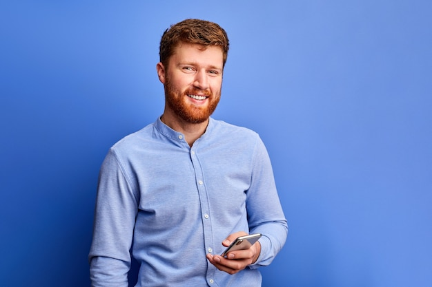 Homem otimista está conversando com um amigo no celular, digitando mensagem, vestindo camisa formal azul, sorrindo