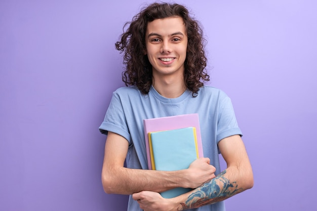Homem otimista positivo com cabelo longo cacheado segurando livros nas mãos, indo para a universidade casualmente ...