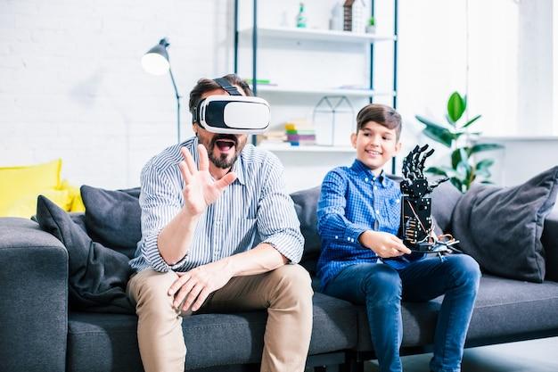 Homem otimista usando óculos de realidade virtual enquanto testa o robô com seu filho