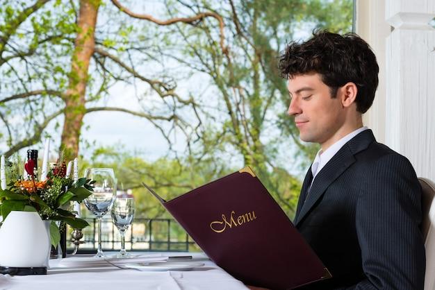Homem ou empresário almoçando negócios em um restaurante requintado e escolhendo no cardápio