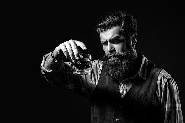 Homem ou empresário bebe whisky em fundo preto. barbudo e copo de uísque.