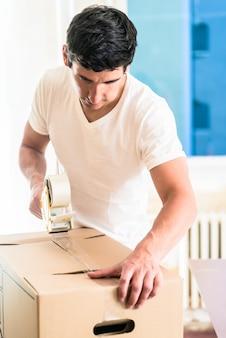Homem ou faz-tudo gravando caixa de embalagem