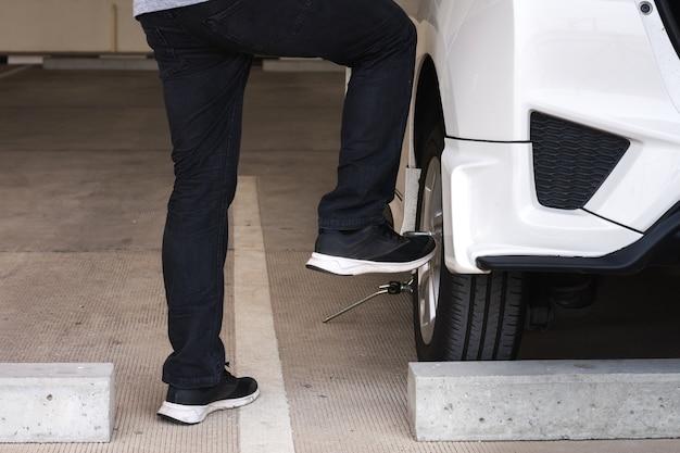 Homem ou trabalhador de mecânico de automóveis trocar o pneu do carro ou fazer manutenção por motivos de segurança.