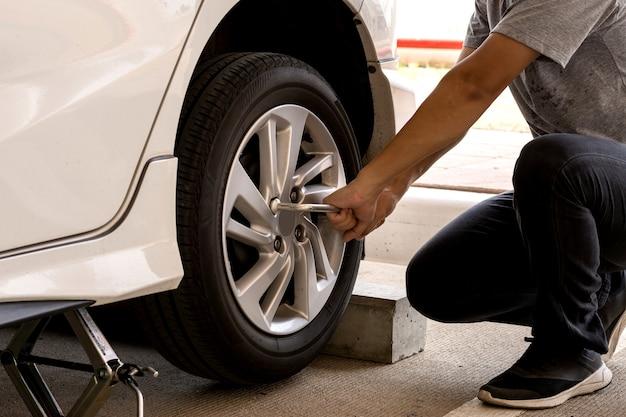 Homem ou trabalhador mecânico de automóveis trocar o pneu do carro ou fazer a manutenção antes de viajar por questões de segurança.