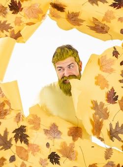 Homem outono brincando com folhas e se preparando para a venda de outono. homem alegre de outono no parque em fundo isolado. outono pessoas felizes.