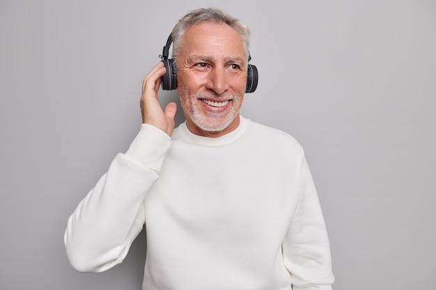 Homem ouve faixa de áudio em fones de ouvido sem fio sorri com prazer desfruta de boa qualidade de som usa jumper branco puro isolado no cinza.