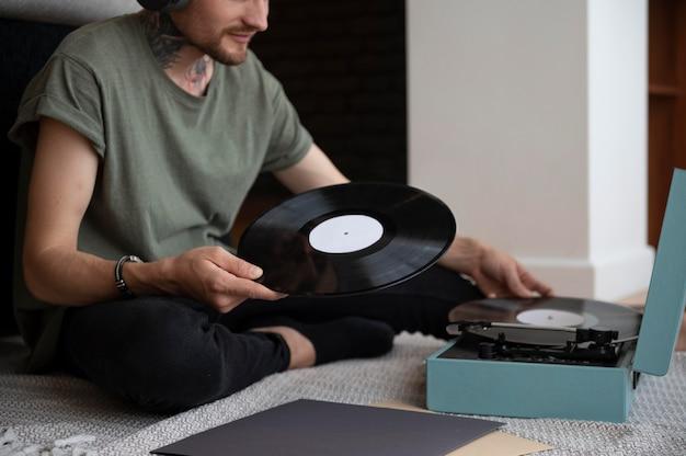 Homem ouvindo música de um disco de vinil