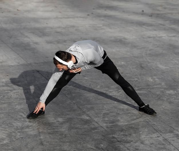 Homem ouvindo música e fazendo exercícios de aquecimento