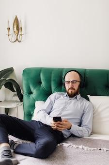 Homem ouvindo música em fones de ouvido na sala de estar
