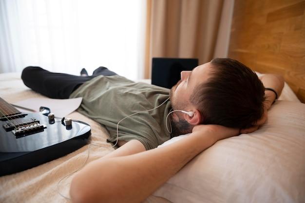 Homem ouvindo música enquanto relaxa na cama