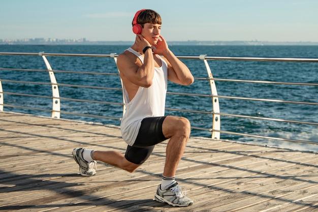 Homem ouvindo música na praia durante o treinamento