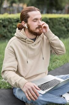 Homem ouvindo música no fone de ouvido ao ar livre