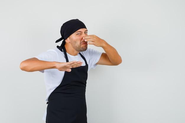 Homem padeiro beliscando nariz devido ao mau cheiro na camiseta