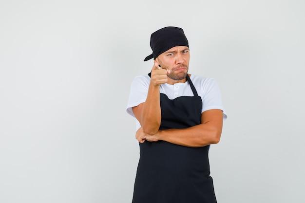 Homem padeiro com camiseta e avental apontando para a câmera e parecendo zangado