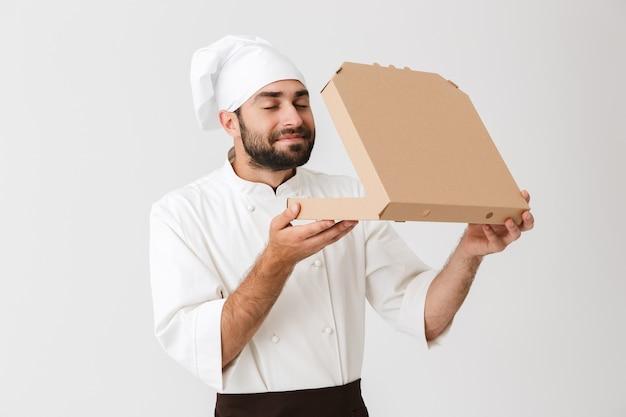 Homem padeiro feliz em uniforme de cozinheiro cheirando enquanto segura uma caixa de pizza isolada na parede branca
