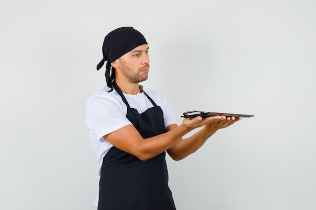 Homem padeiro segurando uma bandeja metálica em uma camiseta