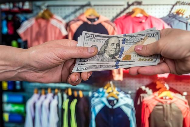 Homem paga em dólares para comprar roupas em uma loja. conceito de compras