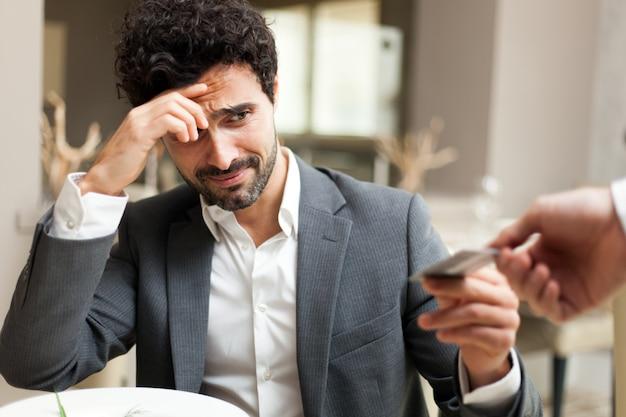 Homem pagando a conta com um cartão de crédito e se sentindo mal porque a soma é muito alta
