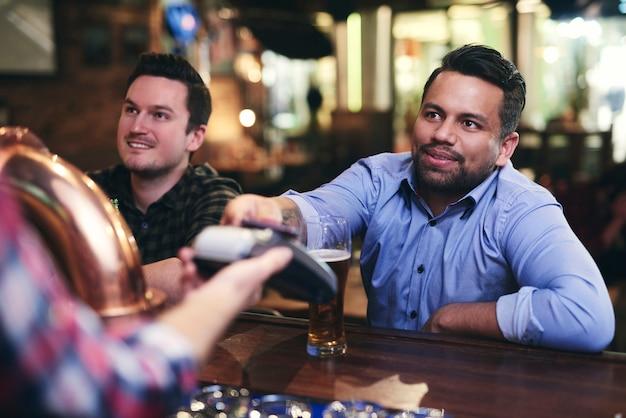 Homem pagando cerveja com cartão de crédito