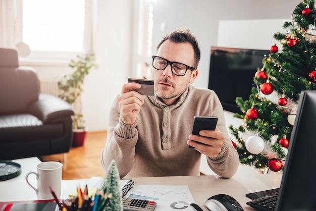 Homem pagando com cartão de crédito no telefone inteligente