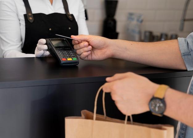 Homem pagando comida para viagem com cartão de crédito