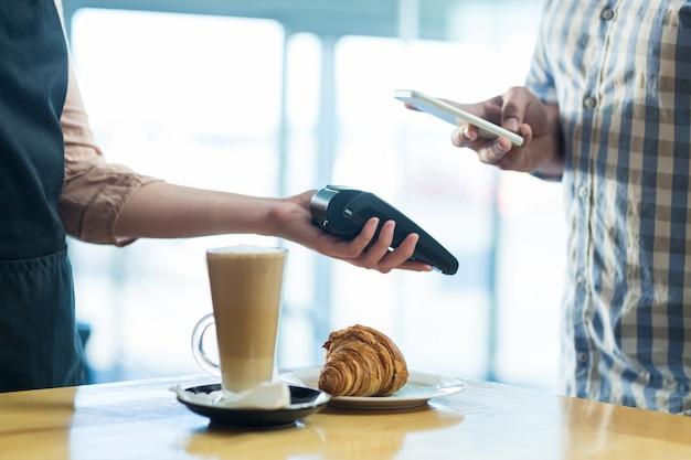 Homem pagar conta através de smartphone usando a tecnologia nfc