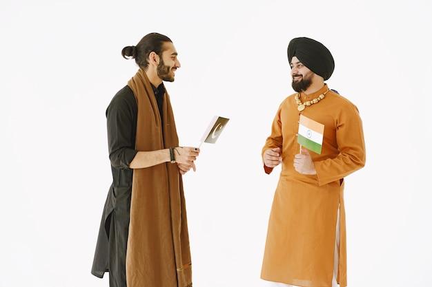 Homem paquistanês e indianos em roupas tradicionais. os amigos estão conversando em fundo branco, isolado. acordo entre países.