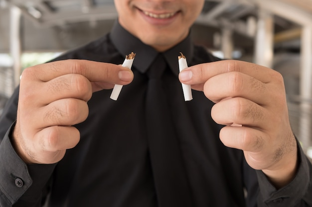 Homem para de fumar, quebrar o cigarro, conceito de decisão de estilo de vida saudável
