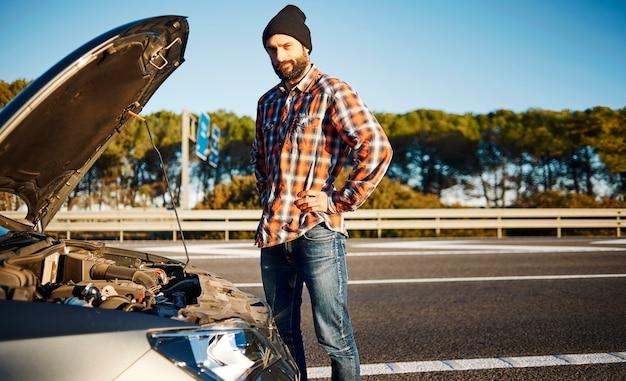 Homem parado ao lado de seu carro quebrado