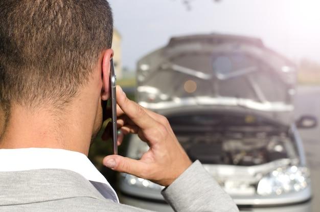 Homem parado ao lado do veículo quebrado chamando o serviço de reboque