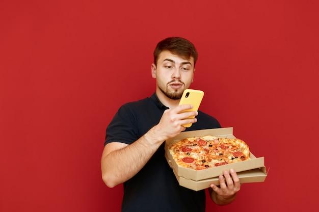 Homem parado com uma caixa de pizza na mão e fazendo uma foto