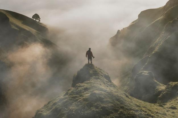 Homem parado em um penhasco com textura de nevoeiro