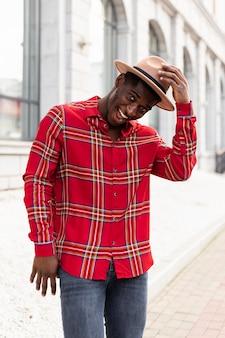 Homem parado gesticulando com o chapéu