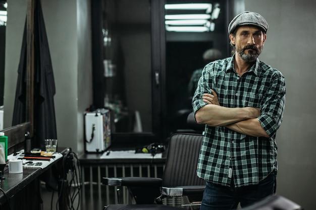 Homem parado na barbearia com os braços cruzados e olhando