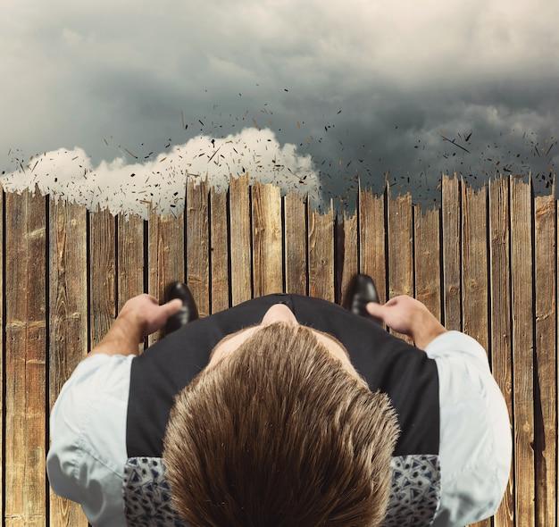 Homem parado na beira das nuvens