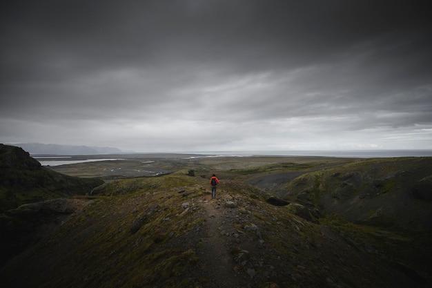 Homem parado na beira de uma montanha
