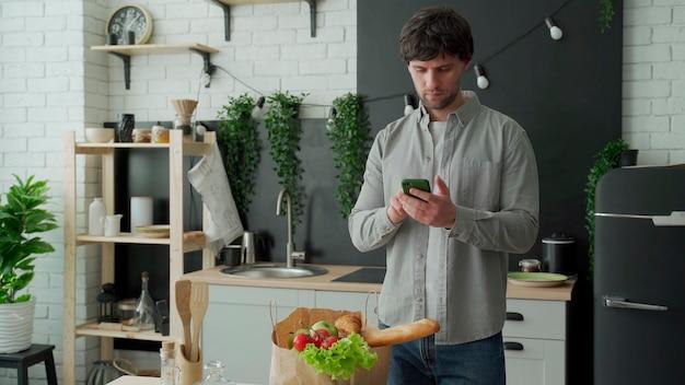 Homem parado na cozinha perto de um saco de papel cheio de comida fresca e usa um aplicativo de smartphone para entregá-lo ao supermercado