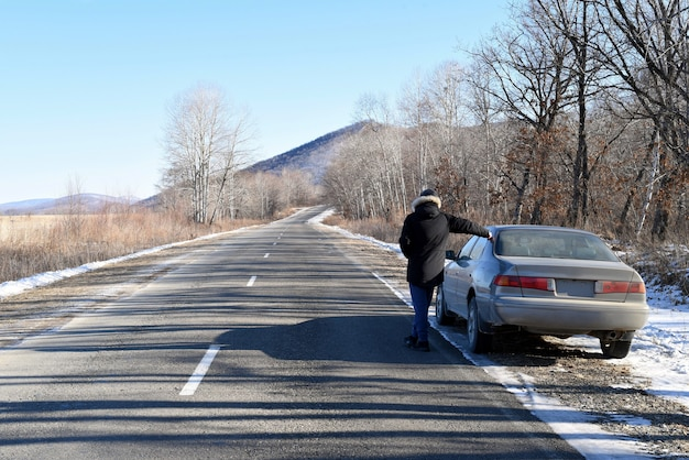 Homem parado na estrada ao lado do carro, olhando para frente