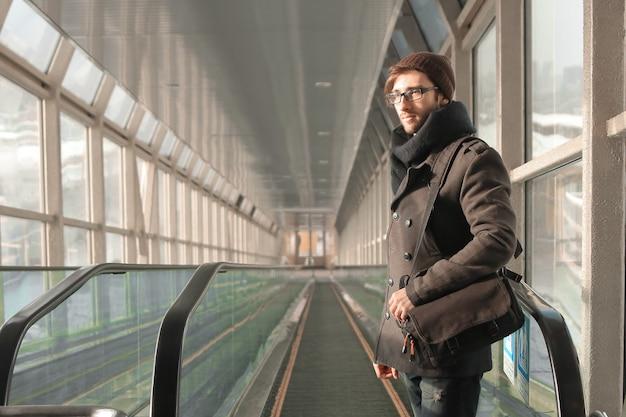 Homem parado na frente da escada rolante na passagem subterrânea