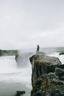 Homem parado no penhasco de uma queda de água épica