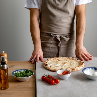 Homem parado perto da massa de pizza assada com ingredientes
