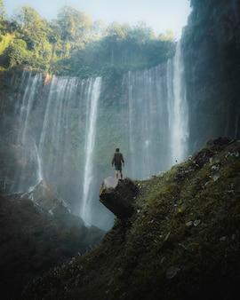 Homem parado perto das cachoeiras tumpak sewu, indonésia