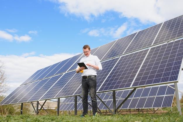 Homem parado perto de painéis solares o painel solar produz energia solar ecológica e ecológica